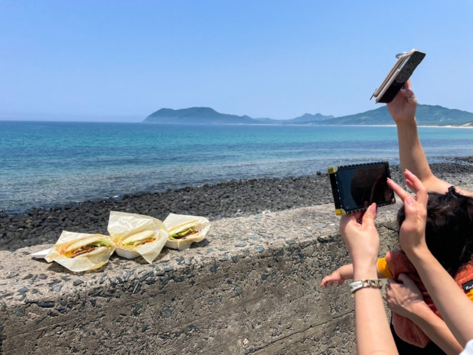 『SANTA MONICA(サンタモニカ)糸島』前の海を背景にバーガーを撮影