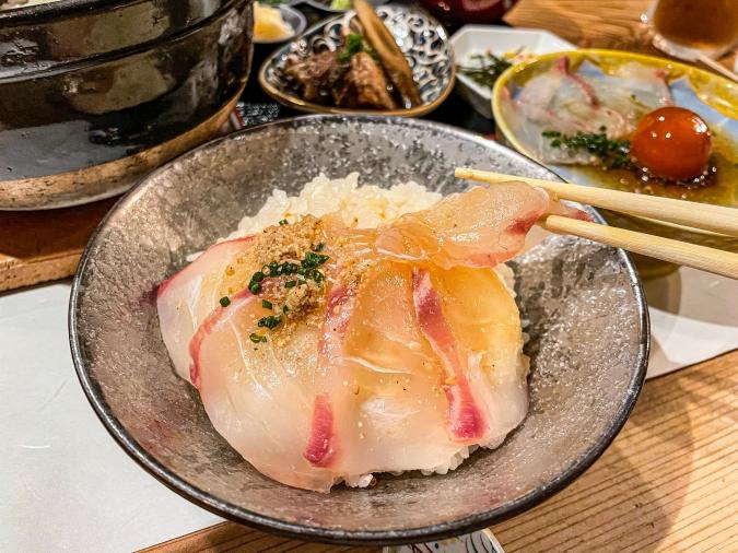 「熾火や 魚二(おきびやうおに)」鯛めし土鍋堪能御膳・鯛めしに鯛刺身を乗せているシーン